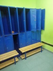 wnętrze szatni z zielonymi ścianami i niebieskimi szafkami