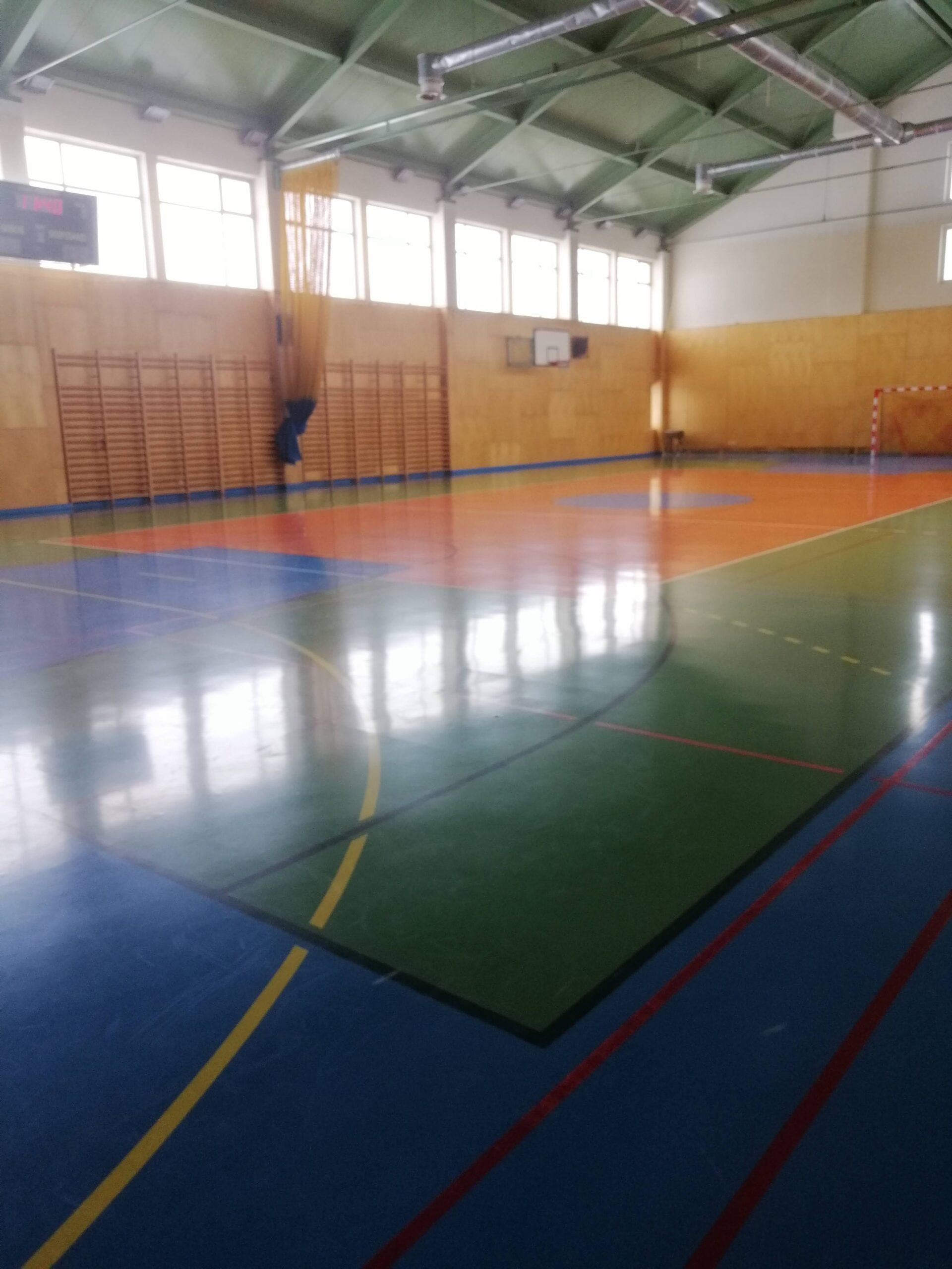 duża sala gimnastyczna z niebiesko-zielono-czerwoną posadzką