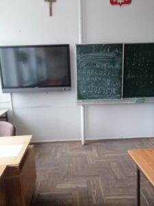 klasa. widok z perspektywy ucznia na tablicę do pisania. obok tablicy na ścianie telewizor