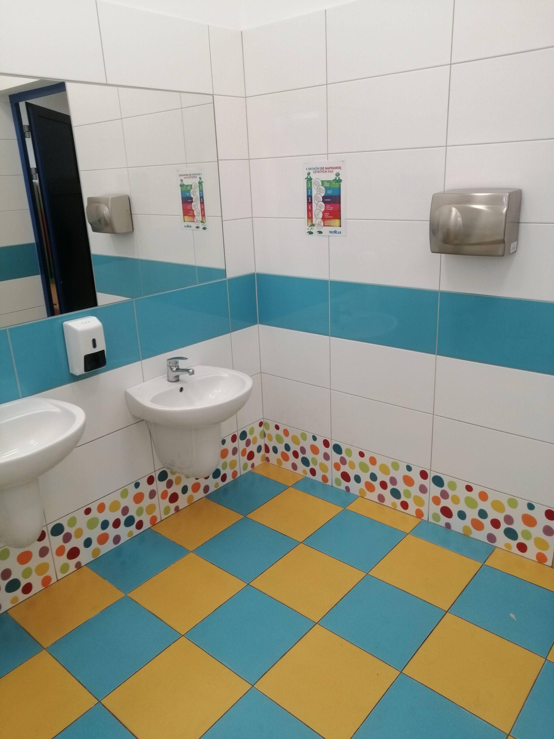 szkolna toaleta z niebiesko-żółtą posadzką