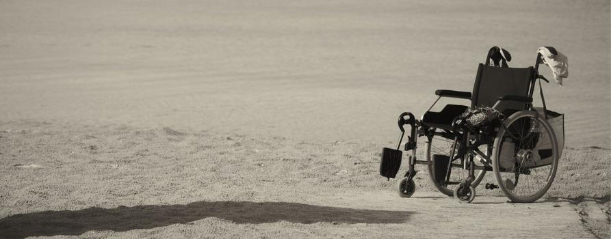 czarno-białe zdjęcie wózka inwalidzkiego na pustej plaży