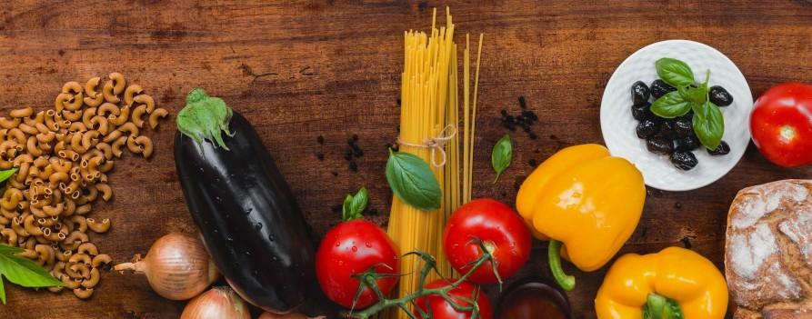 Drewniany blat, na którym położone są umyte warzywa: bakłażan, pomidory, papryka żółta, oliwki, cebula, bazylia oraz makarony pełnoziarniste i chleb.
