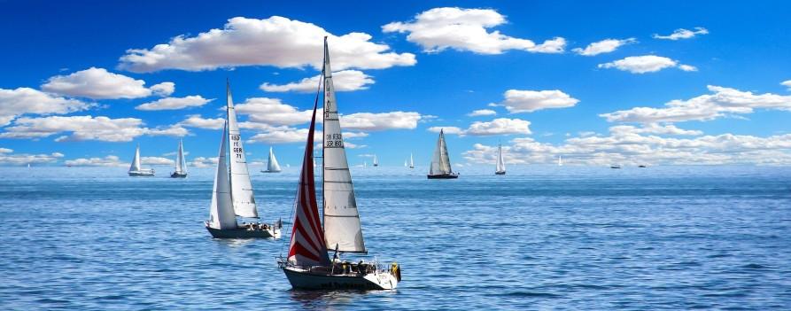Na pierwszym planie łódź żaglowa na błękitnej tafli jeziora, za nią wiele innych podobnych łodzi. W tle błękitne niebo i wiele białych, drobnych chmur.