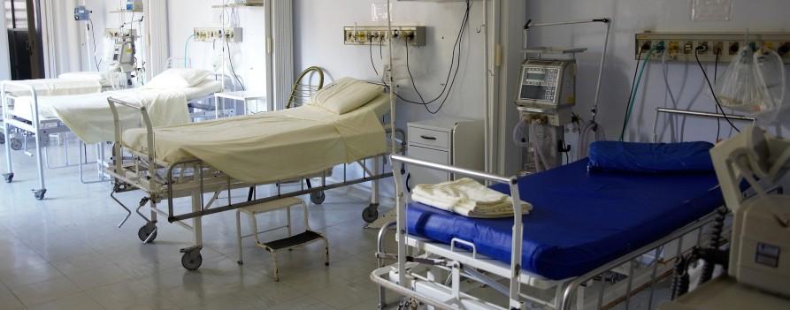 Sala szpitalna z łózkami i podłączonym do nich sprzętem medycznym